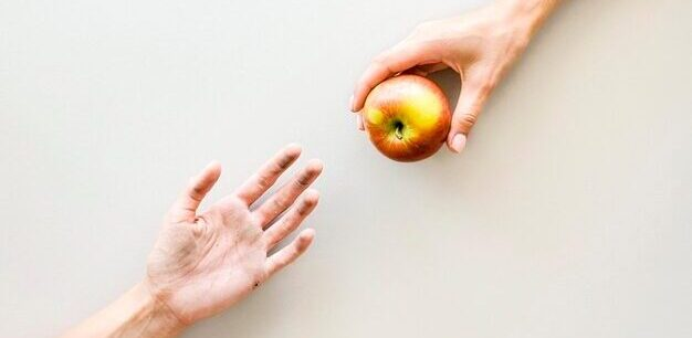Brexit and Food Poverty Hand giving apple to another hand